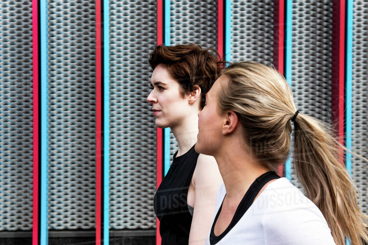 Two young female runners talking on city sidewalk, head and shoulders Royalty-free stock photo