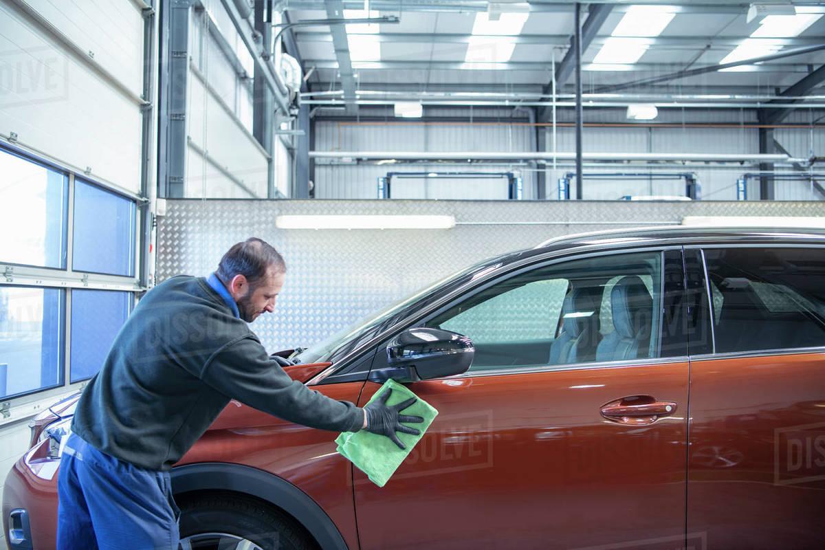 Worker valeting car in car dealership Royalty-free stock photo