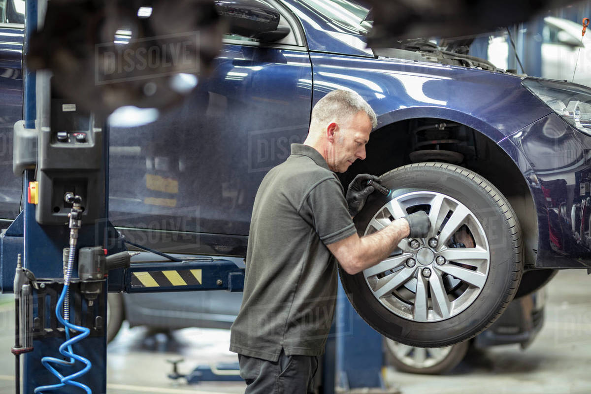 Engineer checking brakes in car service centre Royalty-free stock photo