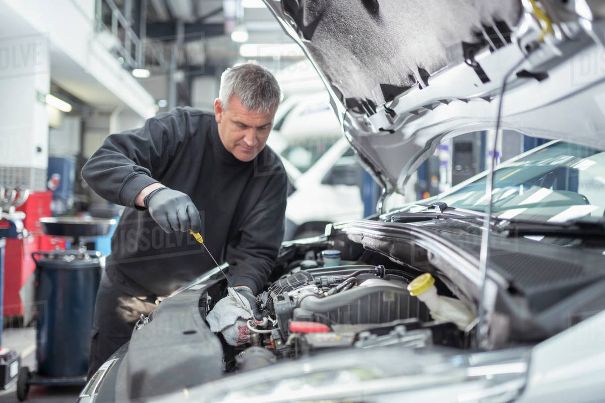 Engineer checking oil level in car service centre Royalty-free stock photo