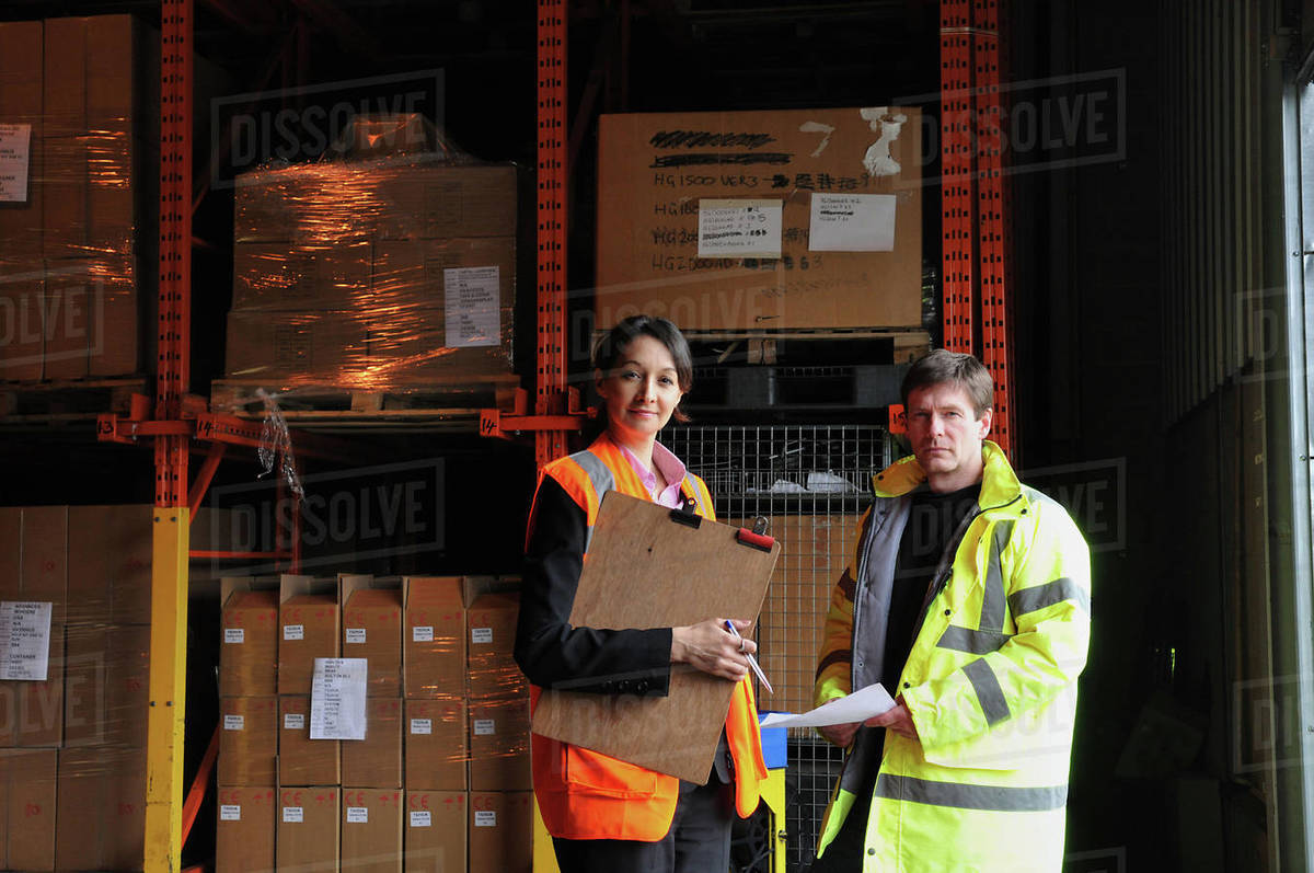 Male and female factory workers with clipboard in warehouse, portrait Royalty-free stock photo