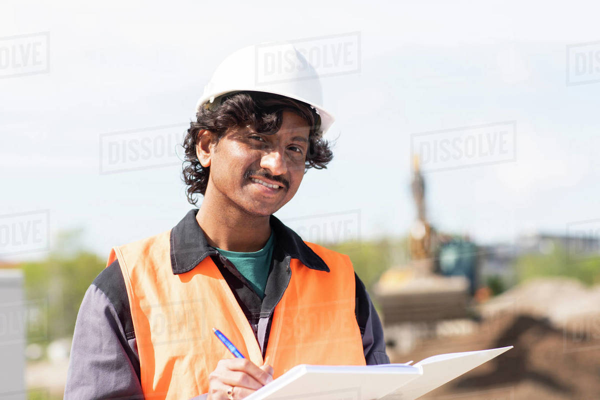 Male engineer on construction site writing in notebook, head and shoulder portrait Royalty-free stock photo