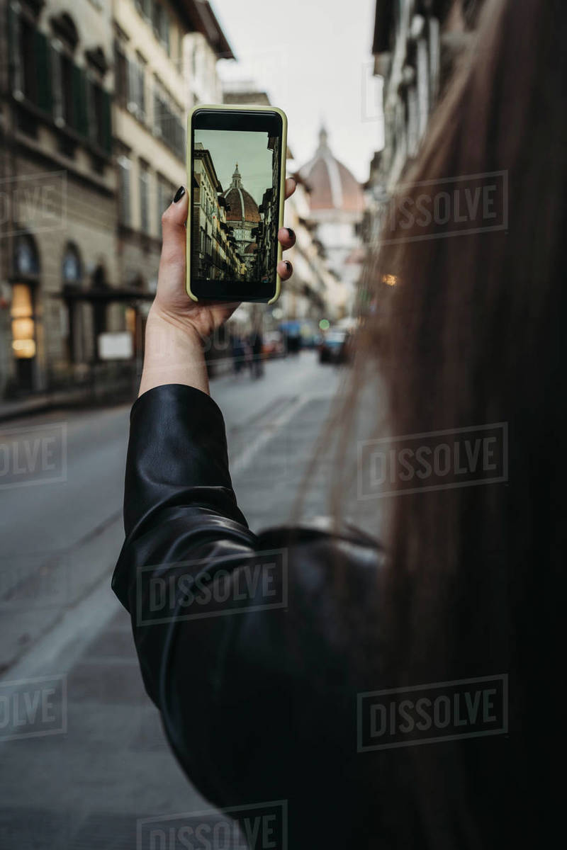 Woman taking photograph of buildings in city Royalty-free stock photo
