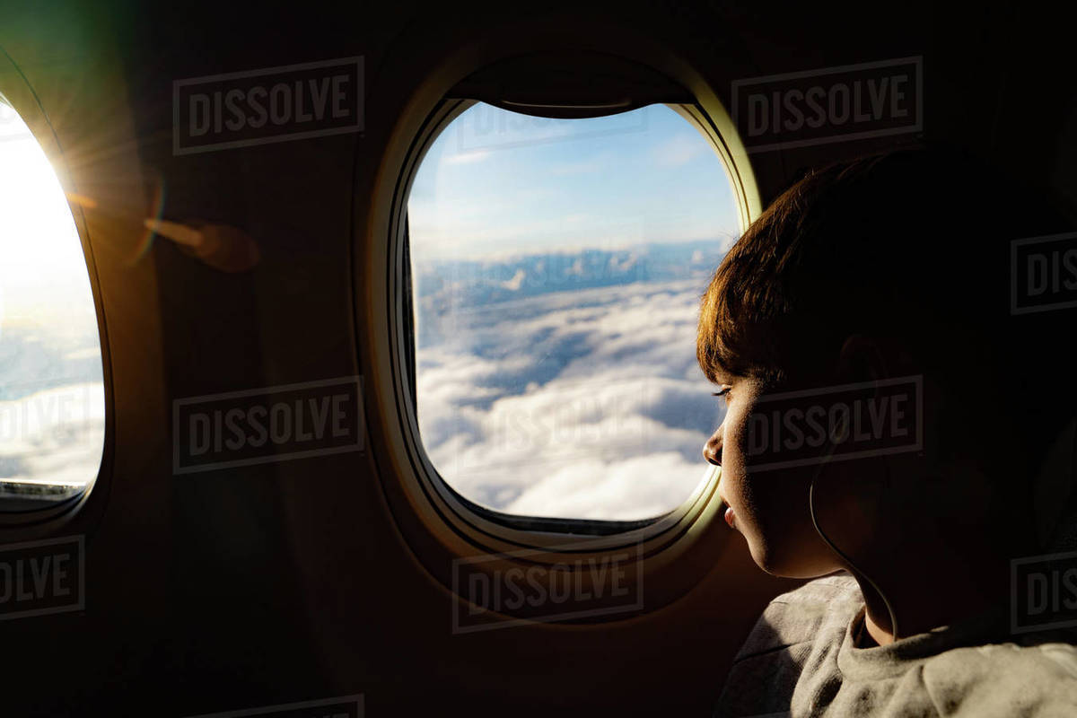 Teenage boy looking out through airplane window at clouds on airplane journey Royalty-free stock photo
