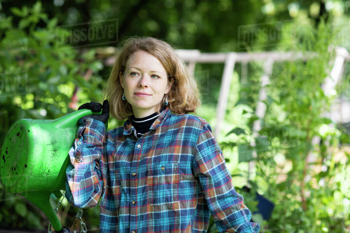 Mid adult woman carrying watering can in her garden Royalty-free stock photo