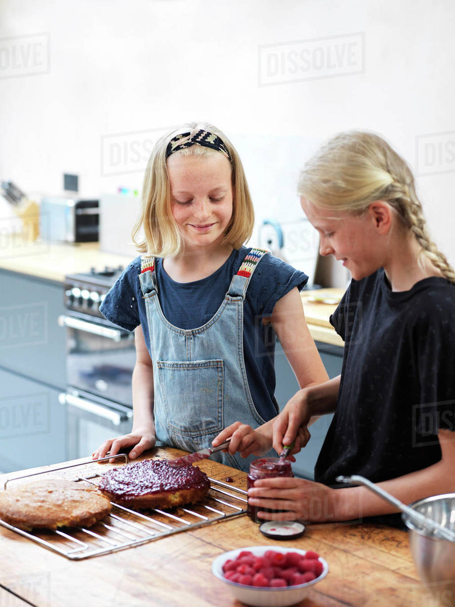 Girl and her sister baking a cake, smoothing jam onto cake at kitchen table Royalty-free stock photo