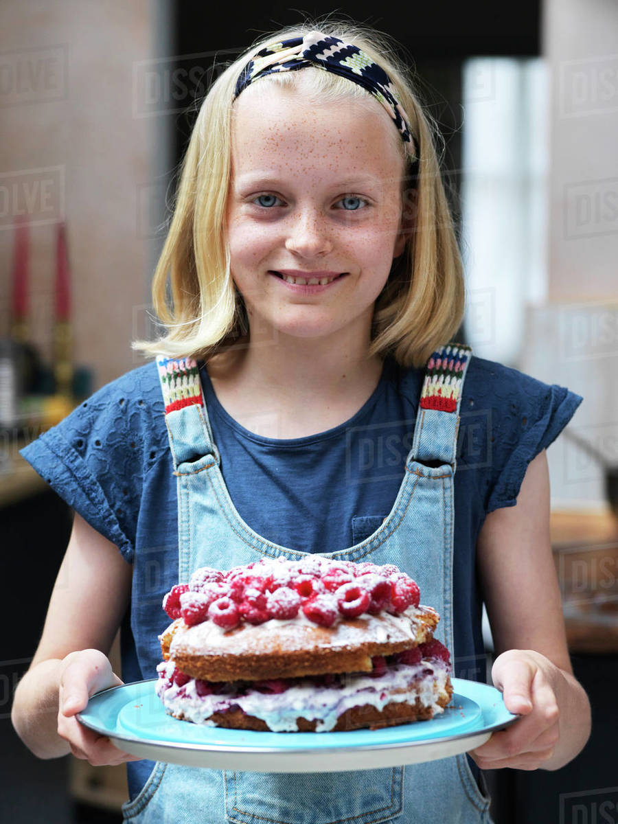 Girl baking a cake, holding homemade cake with raspberries on top in kitchen, portrait Royalty-free stock photo