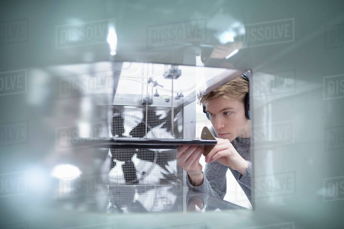 Two male scientists wearing white lab coats performing experiment in wind tunnel in research facility. Royalty-free stock photo