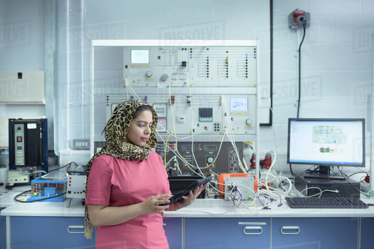 Female electrical engineer standing in front of electrical supply test rig in research facility. Royalty-free stock photo