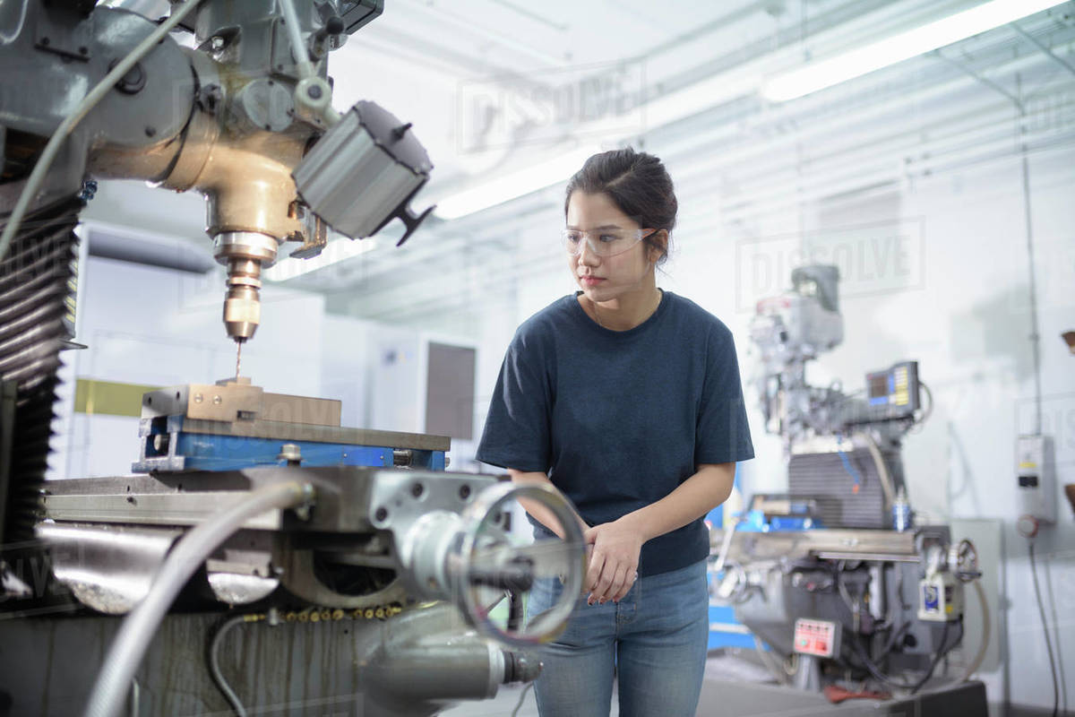 Female engineer working with drill in engineering factory. Royalty-free stock photo