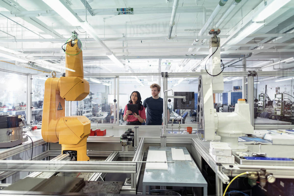 Male and female trainee engineers with robotic equipment in research facility. Royalty-free stock photo