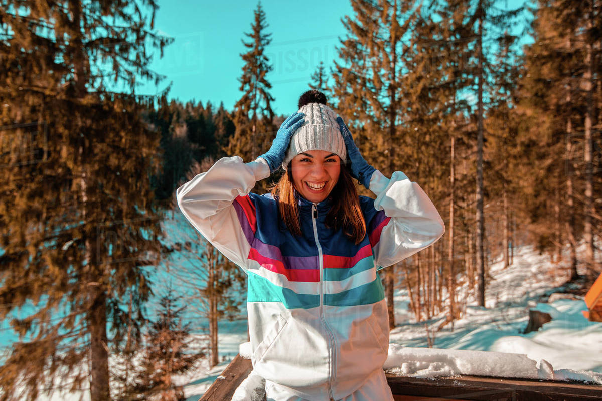 A woman wearing a ski jacket and woolly hat with hands on her head in woodland Royalty-free stock photo