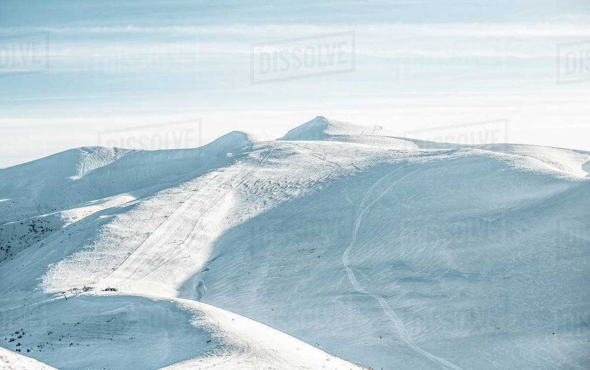 View of deserted ski slopes in the mountains, empty pistes with snow tracks.  Royalty-free stock photo