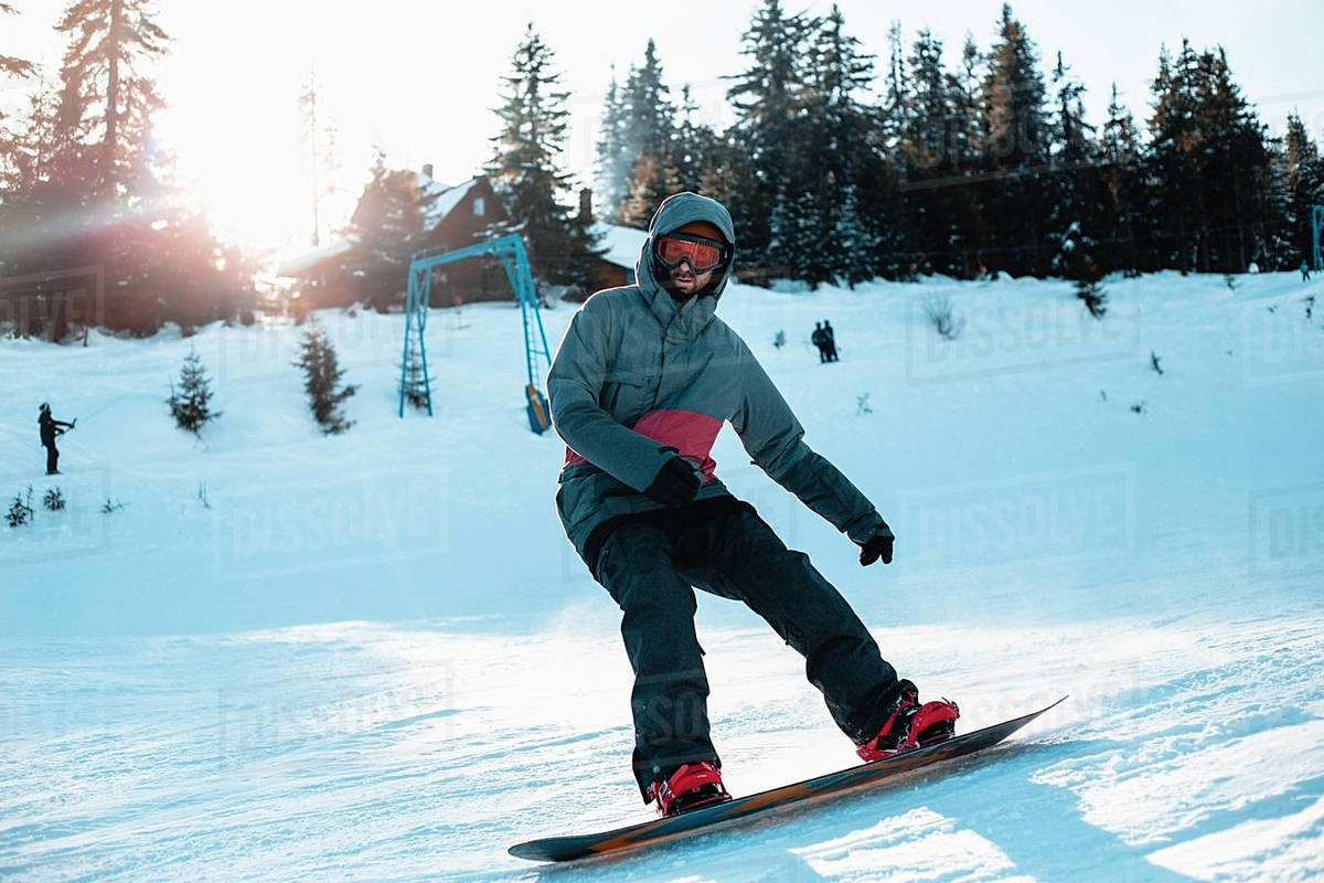 A snowboarder skiing down a snowy slope with trees and a ski lift in the background. Royalty-free stock photo