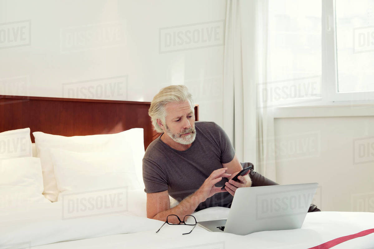 A man lying on a bed looking at his laptop and mobile phone. Royalty-free stock photo