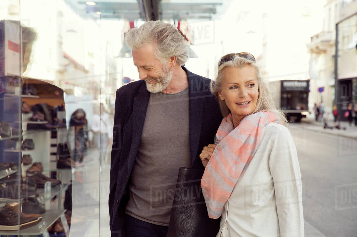 A couple with arms around each other looking in a shop window. Royalty-free stock photo