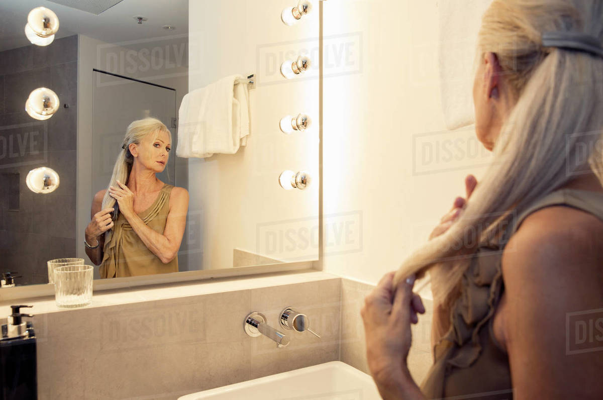 A woman looking in a bathroom mirror and smoothing her long ponytail. Royalty-free stock photo