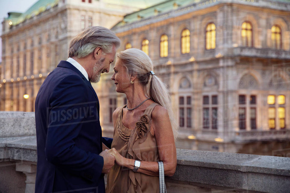 A couple facing each other and standing close holding hands with a Vienna building in the background. Royalty-free stock photo