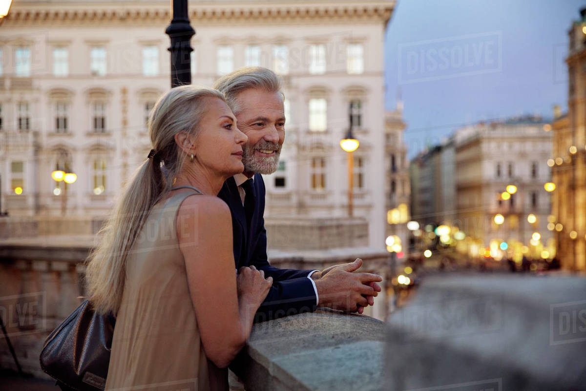 A couple leaning against a balustrade overlooking Vienna during the evening. Royalty-free stock photo