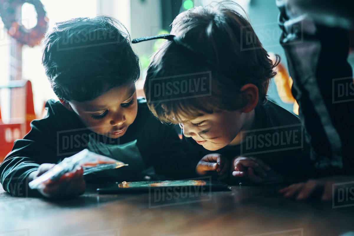 Two children standing next to a table looking at a computer tablet. Royalty-free stock photo