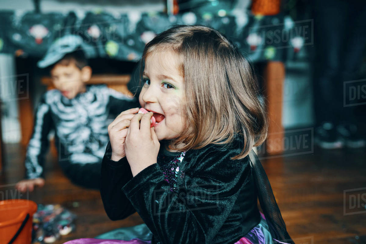 A girl smiling and eating sweets with a boy dressed as a skeleton in the background. Royalty-free stock photo