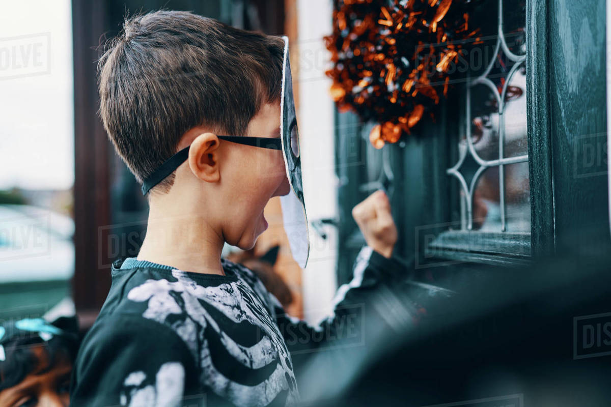 Close up of a boy wearing a mask knocking on a front door at Halloween. Royalty-free stock photo