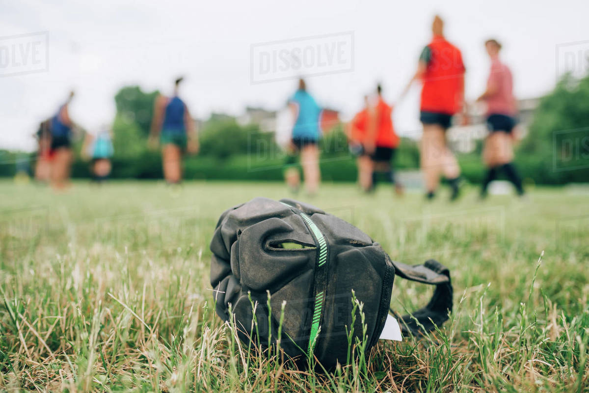 A protective rugby cap on the grass in the foreground with a group of women training in the background.  Royalty-free stock photo