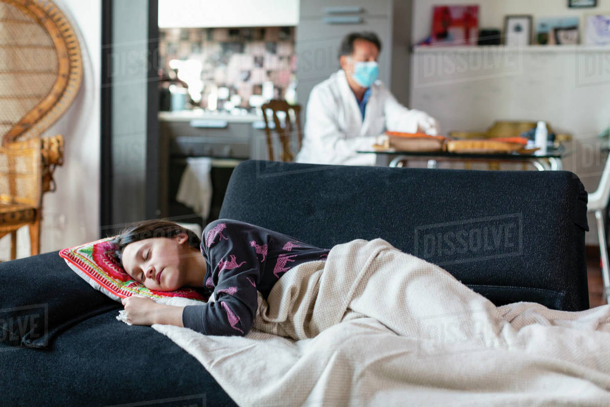Doctor wearing a white coat and facemask sitting at a table and a teenage girl lying on a sofa.  Royalty-free stock photo