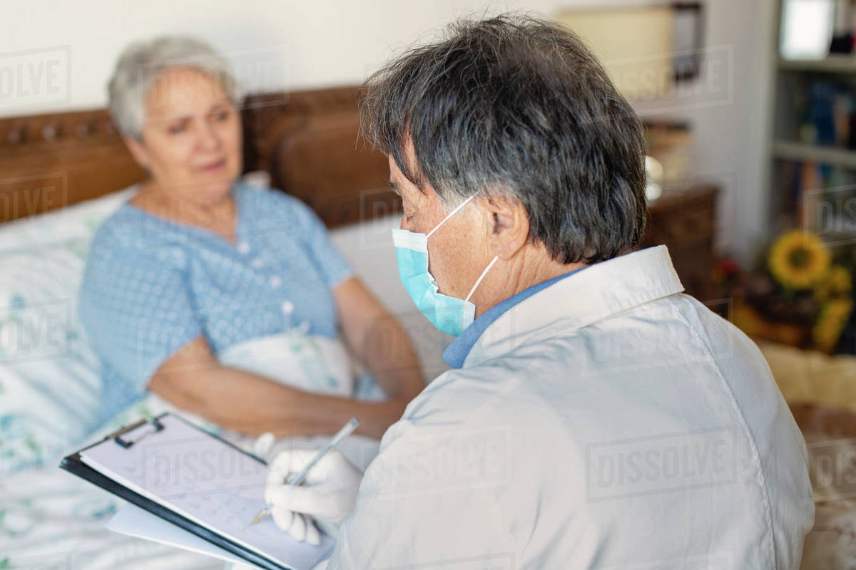 A doctor in a white coat and protective face mask making a home visit to a senior woman patient.  Royalty-free stock photo