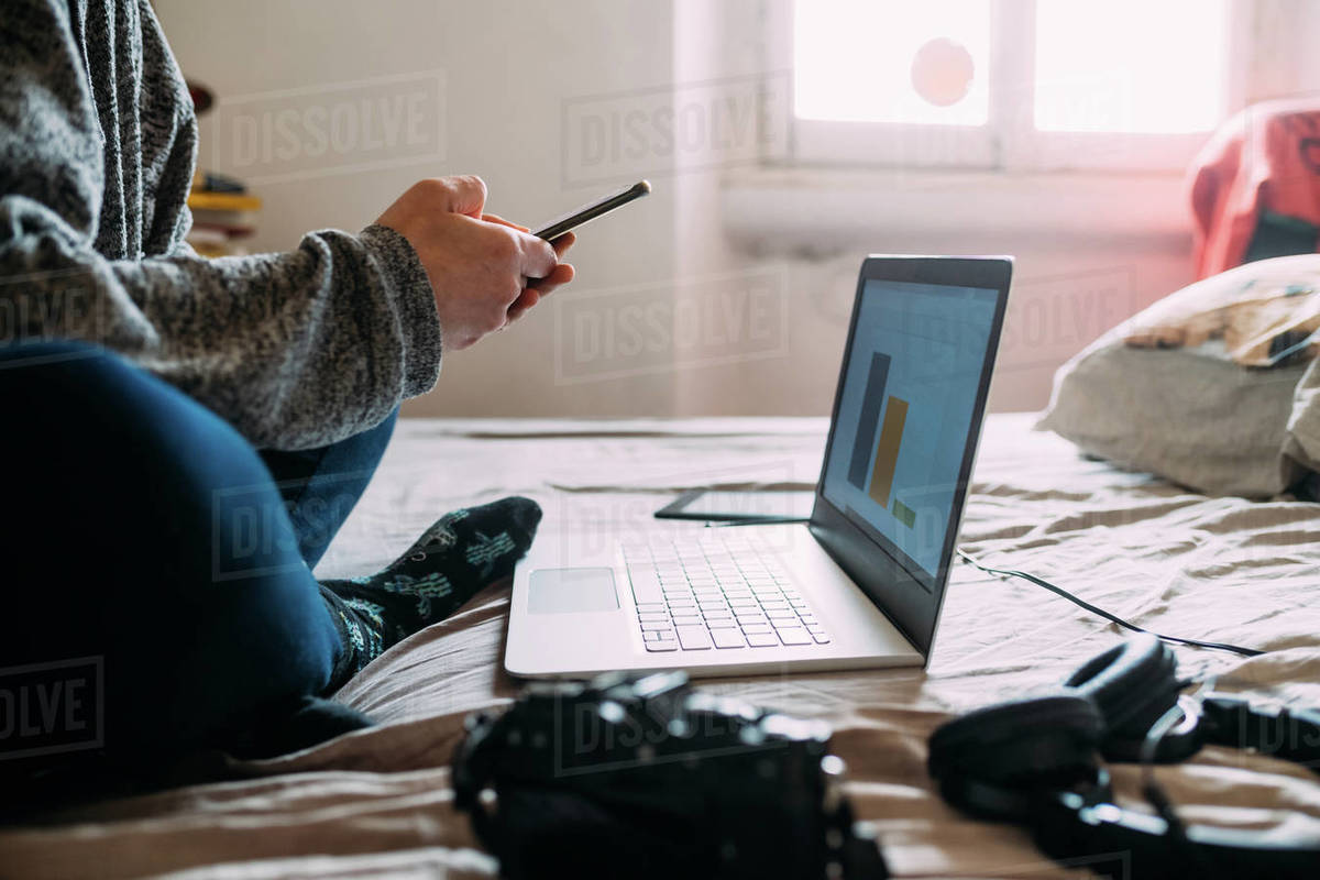 Close up of person sitting on bed, working on mobile phone and laptop computer during Corona virus crisis. Royalty-free stock photo