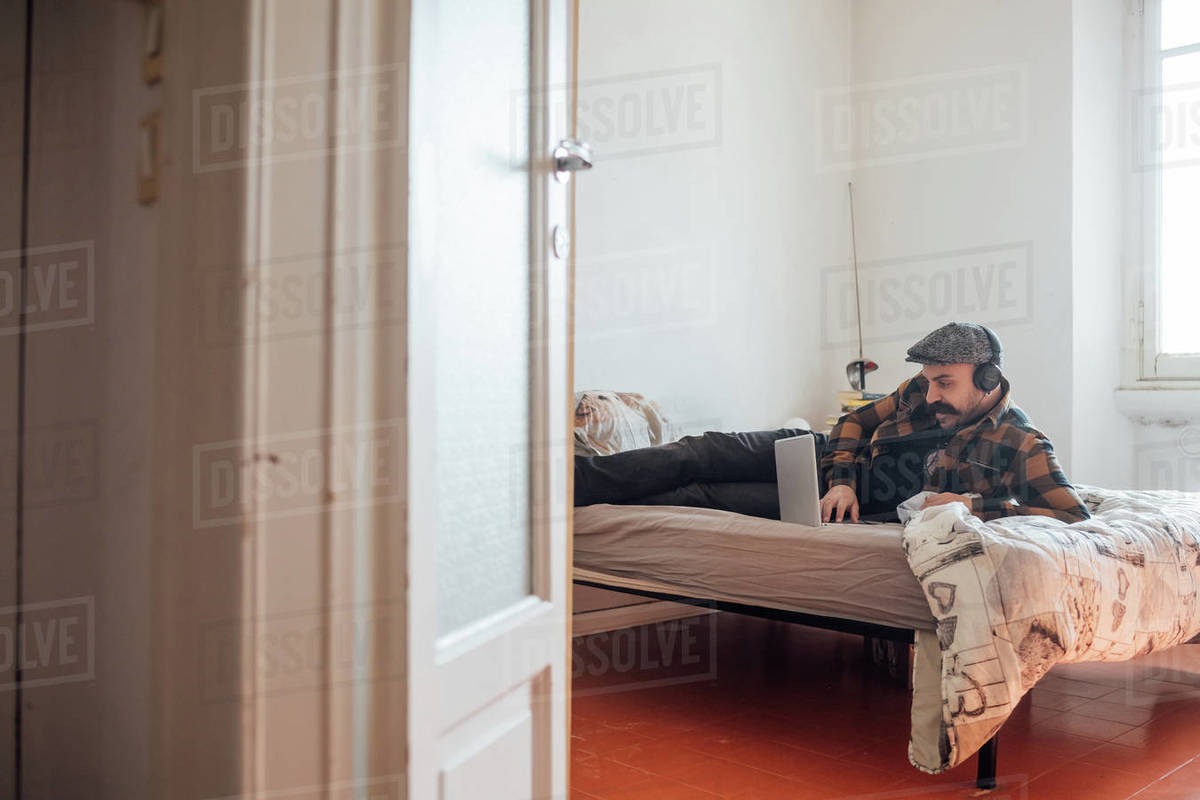 Man with big moustache wearing flat cap and headphones lying on bed with laptop computer during Corona virus crisis. Royalty-free stock photo