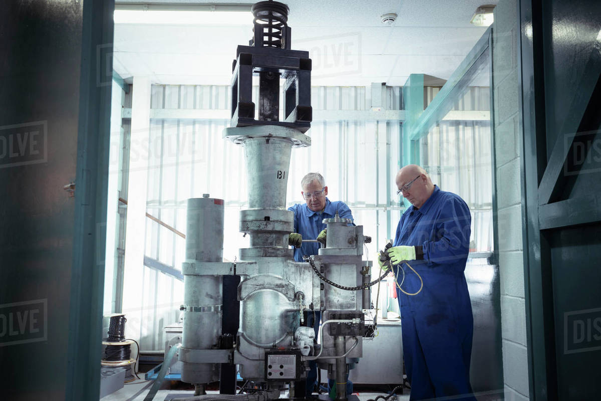 Engineers testing a valve in a nuclear power station. Royalty-free stock photo