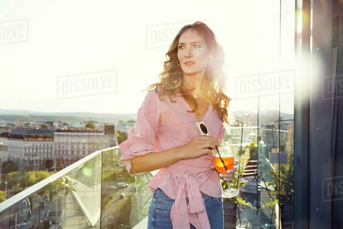 A woman standing on a balcony in the evening sun with a large drink Royalty-free stock photo