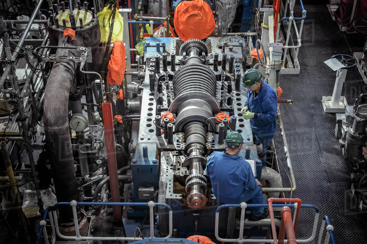 Overhead view of engineers inspecting a turbine in a  nuclear power station. Royalty-free stock photo