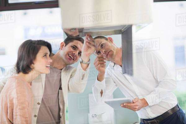 Mid adult couple and salesman looking at extractor hood in kitchen showroom Royalty-free stock photo