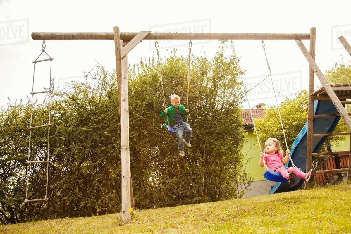 Brother and sister playing on swings in garden - Stock Photo - Dissolve