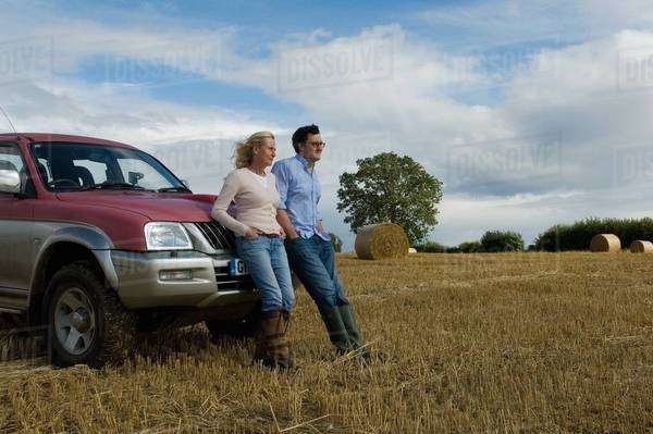 Mother and son leaning against four wheeled drive in harvested field Royalty-free stock photo