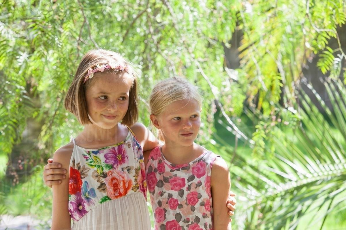 candid portrait of two girls looking away in garden - stock photo