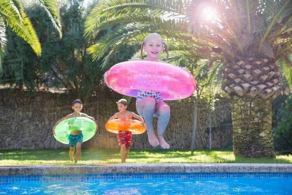 Girl jumping with inflatable ring into garden swimming pool Royalty-free stock photo