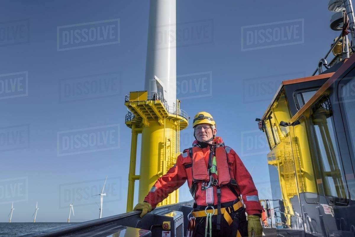 Portrait of engineer on boat on offshore wind farm stock photo