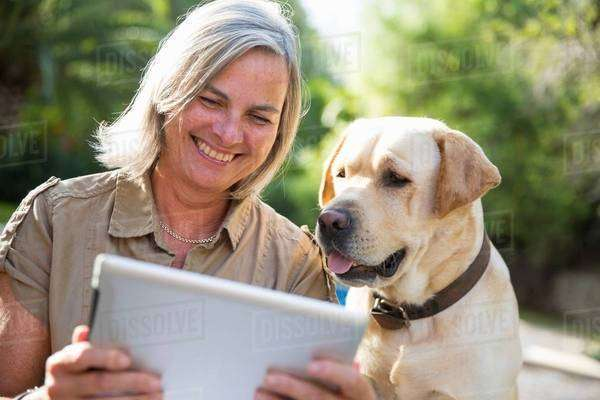 Woman and dog looking at digital tablet Royalty-free stock photo