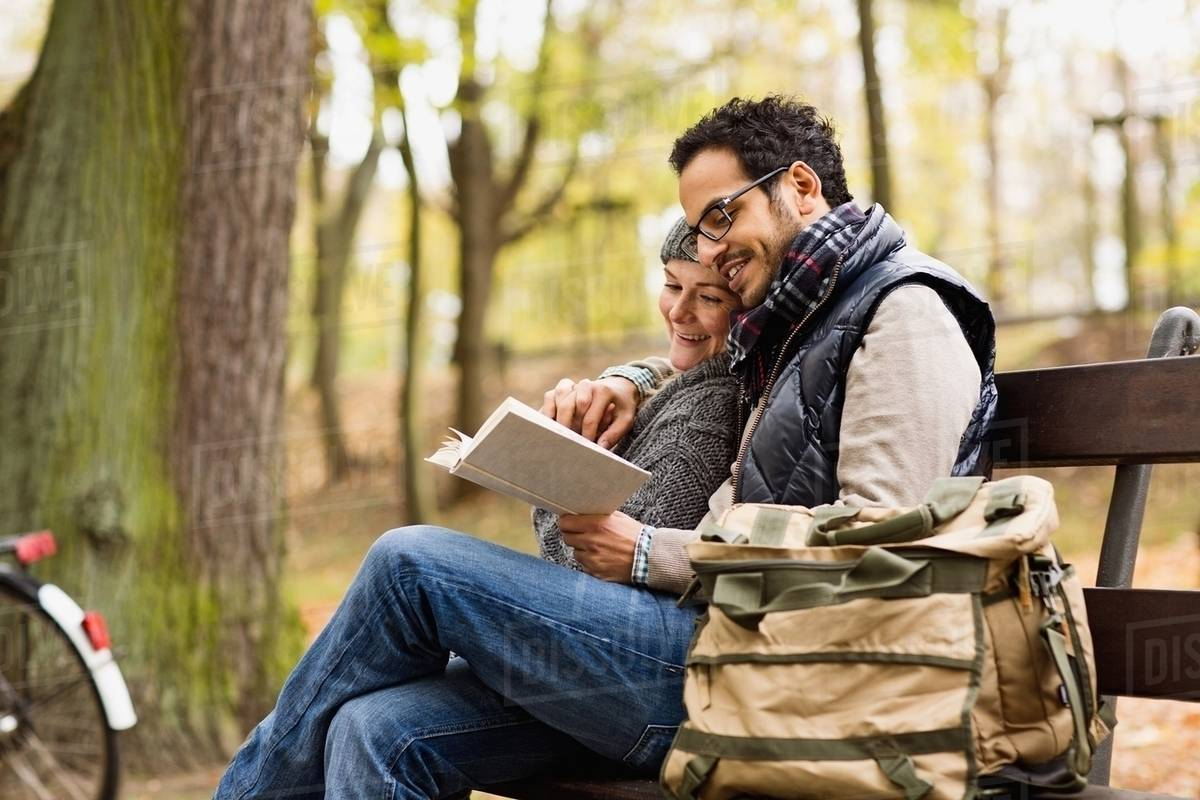 couple reading together on park bench stock photo dissolve