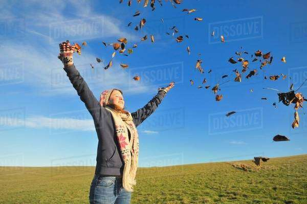 Woman playing in autumn leaves Royalty-free stock photo