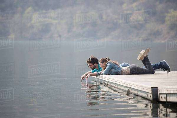 Young couple lying on pier dipping fingers in Lake Mergozzo, Verbania, Piemonte, Italy Royalty-free stock photo
