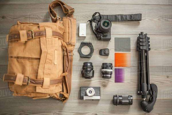 Camera equipment and camera bag arranged on table, overhead view Royalty-free stock photo
