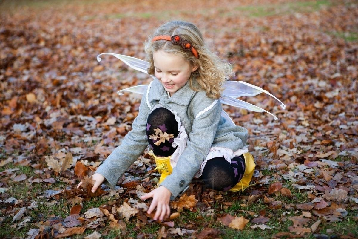 Girl in fairy wings playing in leaves Royalty-free stock photo
