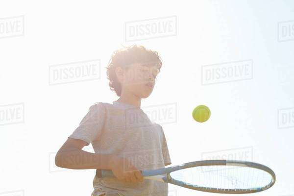 Boy bouncing ball on tennis racket Royalty-free stock photo