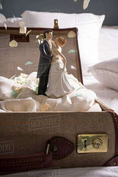 Open suitcase on bed with wedding figurines and confetti Royalty-free stock photo