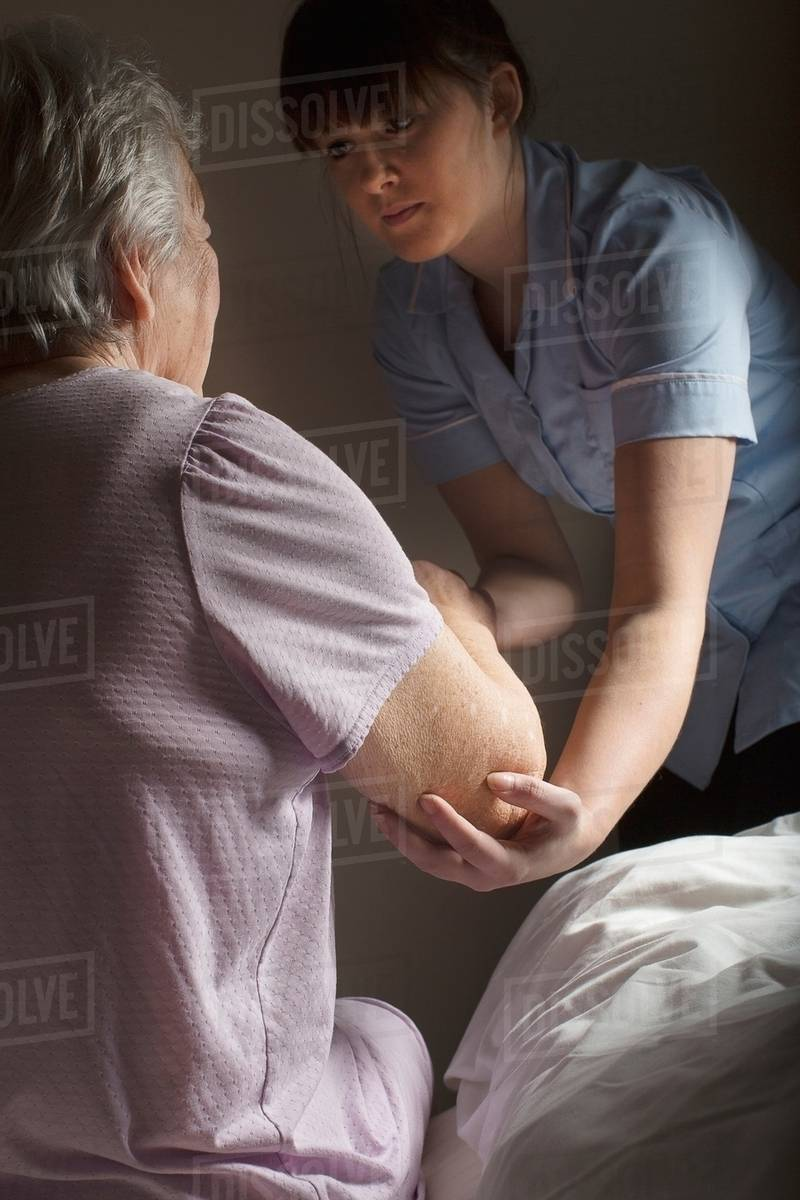 Personal Care Assistant Helping Senior Woman To Get Up Stock Photo