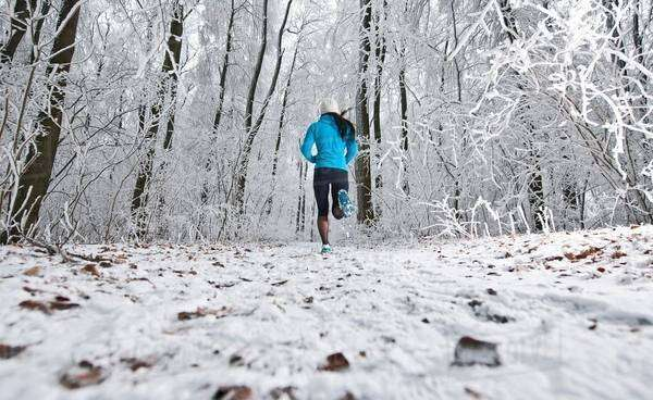 Mature woman jogging in forest in winter snow Royalty-free stock photo